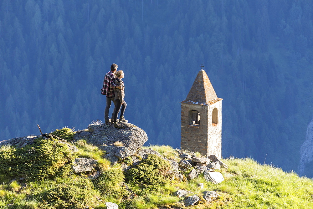 Man and woman embraced look at the bell tower, San Romerio Alp, Brusio, Poschiavo Valley, Canton of Graubunden, Switzerland, Europe - 1179-2465
