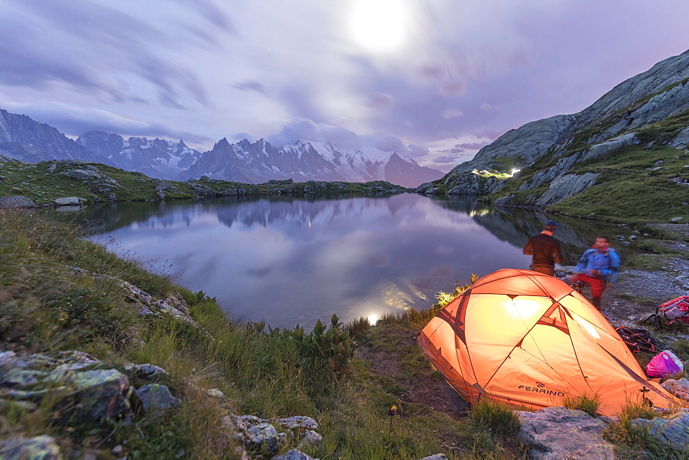 Hikers and tent on the shore of Lacs De Cheserys at night with Mont Blanc massif on background, Chamonix, Haute Savoie, France