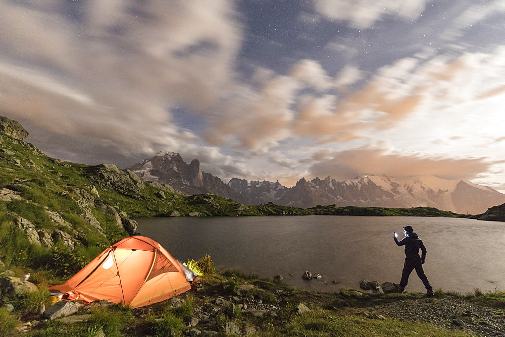 Hiker and tent on the shore of Lacs De Cheserys at night with Mont Blanc massif on background, Chamonix, Haute Savoie, France