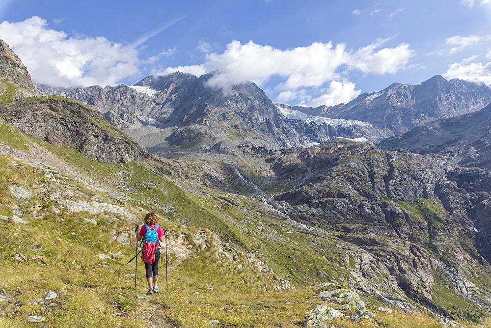 Hiker on path Sentiero Glaciologico with Fellaria Glacier in the background, Malenco Valley, Valtellina, Lombardy, Italy
