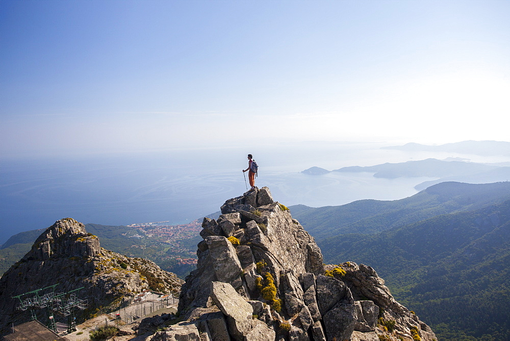 Hiker admires the sea from the top of Monte Capanne, Elba Island, Livorno Province, Tuscany, Italy
