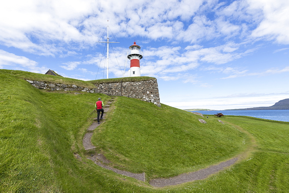 Man walks to the lighthouse and historic fortress of Skansin,Torshavn, Streymoy Island, Faroe Islands, Denmark, Europe