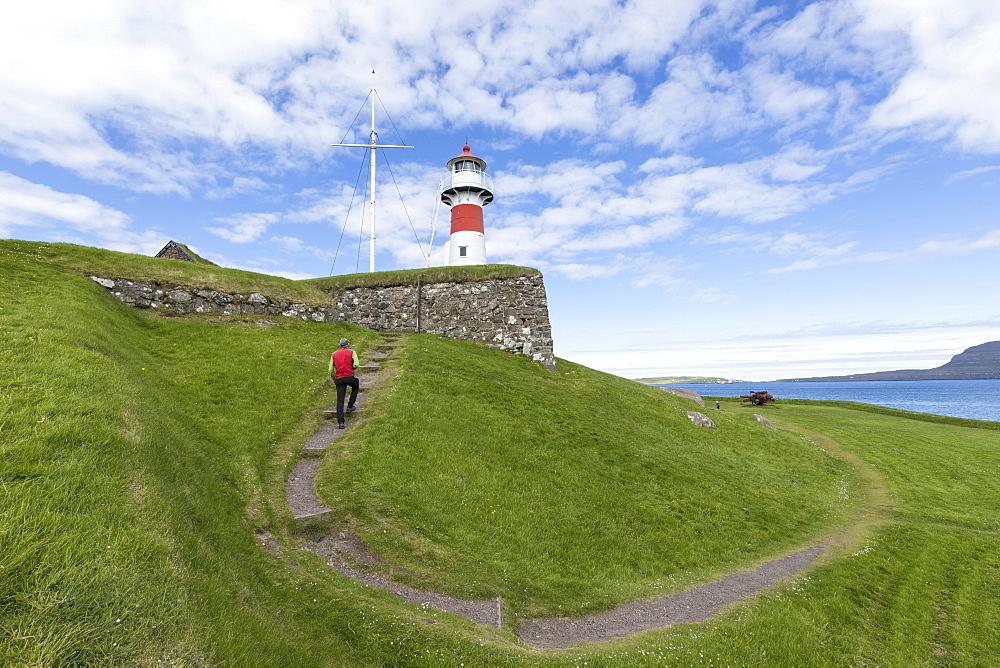Man walks to the lighthouse and historic fortress of Skansin,Torshavn, Streymoy Island, Faroe Islands, Denmark, Europe