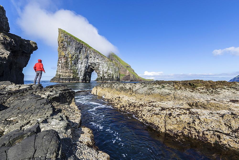Man on cliffs looks towards the natural arch of Drangarnir rock, Vagar Island, Faroe Islands