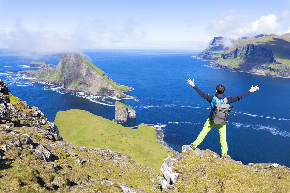 Man on cliffs looks towards Drangarnir rock, Vagar Island, Faroe Island