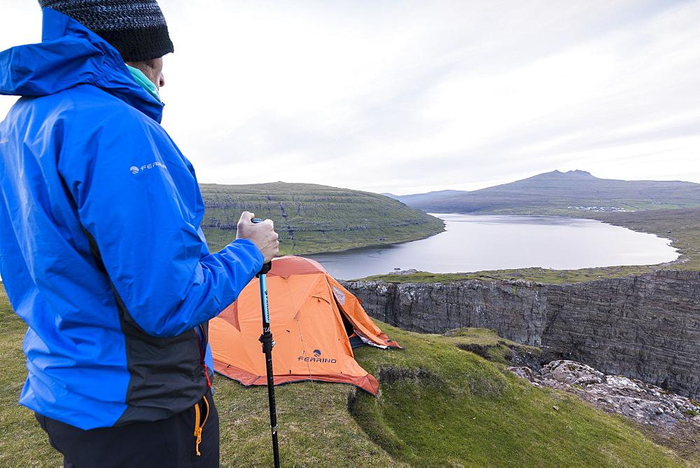 Hiker on cliffs looks towards lake Sorvagsvatn, Vagar Island, Faroe Islands, Denmark, Europe