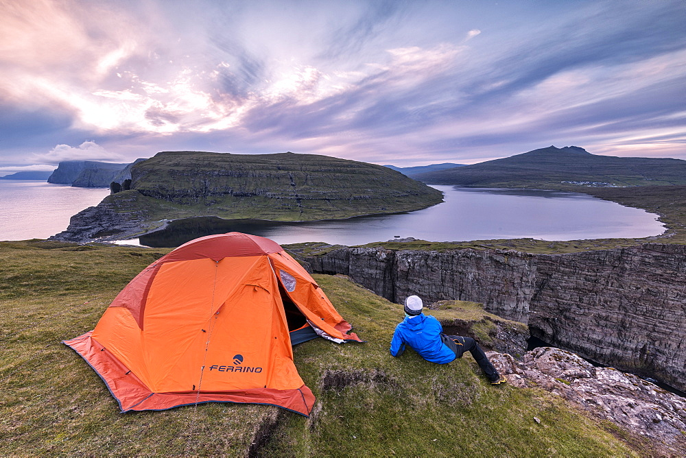 Camping tent and hiker on cliff above lake Sorvagsvatn at sunset, Vagar Island, Faroe Islands