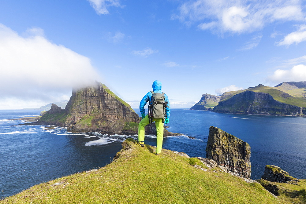 Man looks towards the sea stacks of Drangarnir and Tindholmur islet, Vagar Island, Faroe Islands