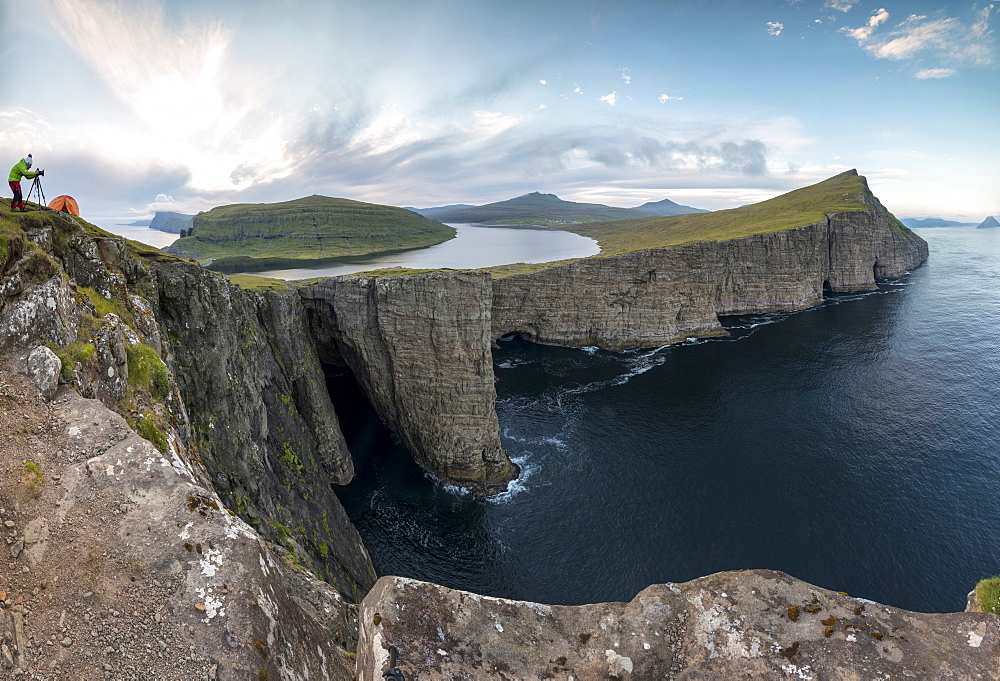 Panoramic of photographer on cliffs above lake Sorvagsvatn, Vagar Island, Faroe Islands, Denmark, Europe