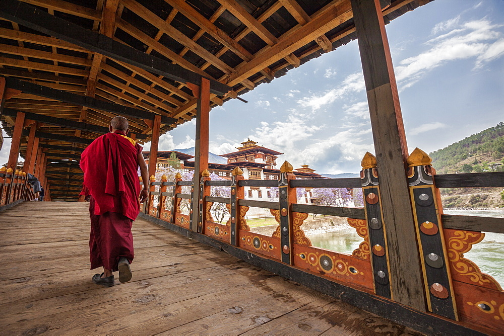 A monk (lama) of Punakha Dzong crosses the wooden bridge over the river that provides access to the ancient monastery, Bhutan, Asia