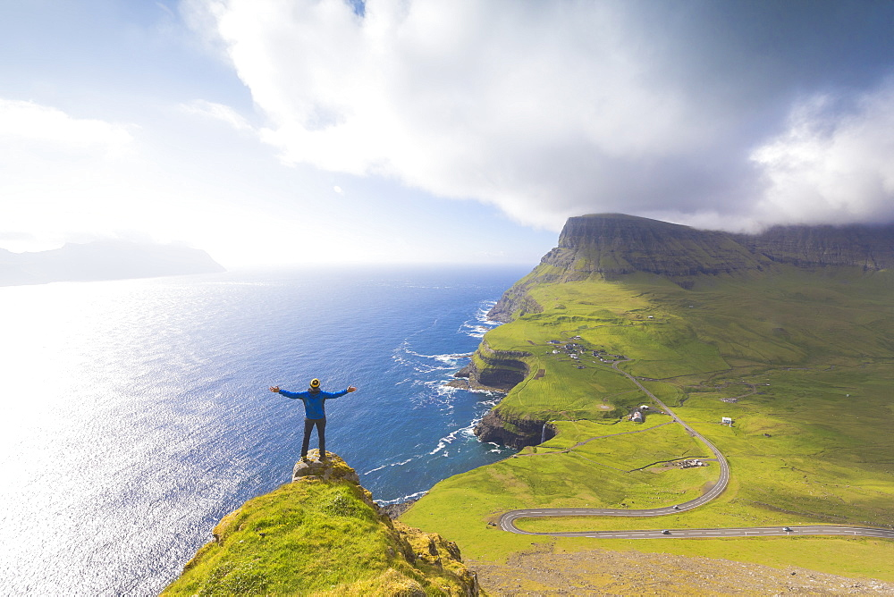 Hiker on top of rocks, Gasadalur, Vagar Island, Faroe Islands, Denmark, Europe