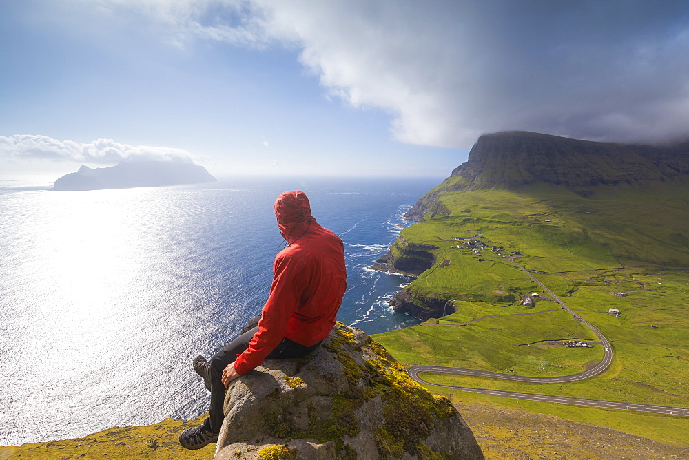 Hiker sitting on rocks looking at the ocean, Gasadalur, Vagar Island, Faroe Islands, Denmark, Europe