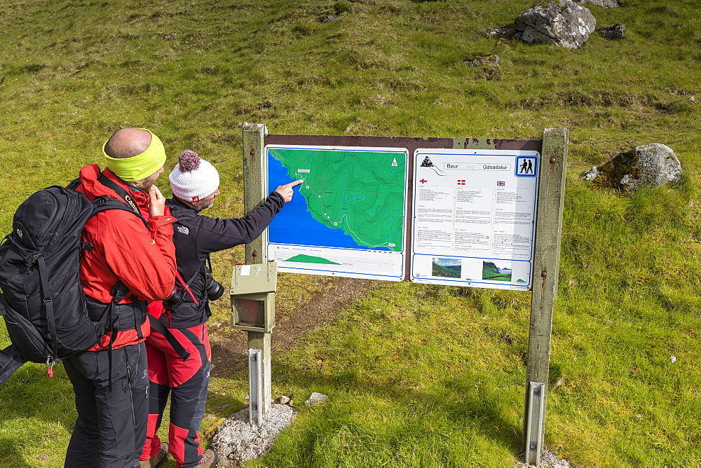 Hikers looking at maps, Gasadalur, Vagar Island, Faroe Islands, Denmark, Europe