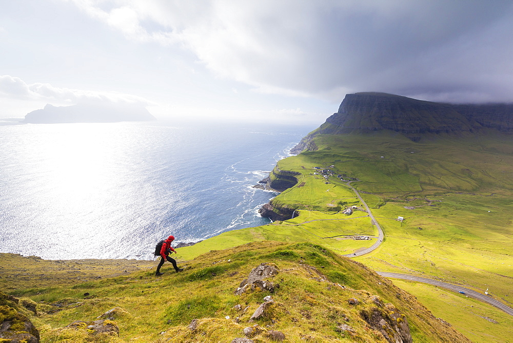 Hiker on steep hills towards Bour, Gasadalur, Vagar Island, Faroe Islands, Denmark, Europe