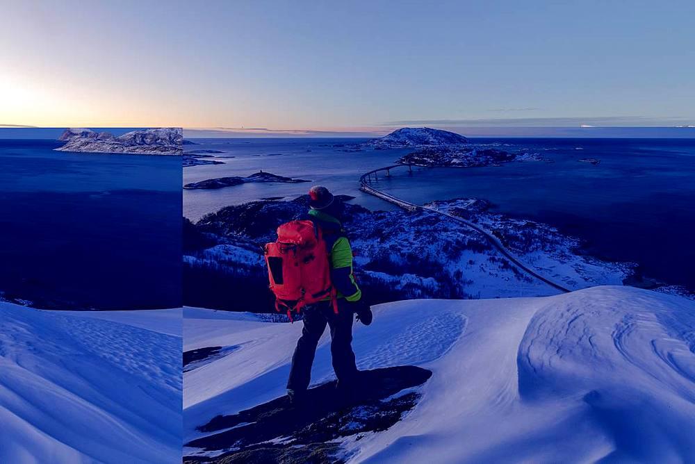 Hiker on snowy peak looks towards bridge and sea, Sommaroy island, Troms county, Norway - 1179-3243