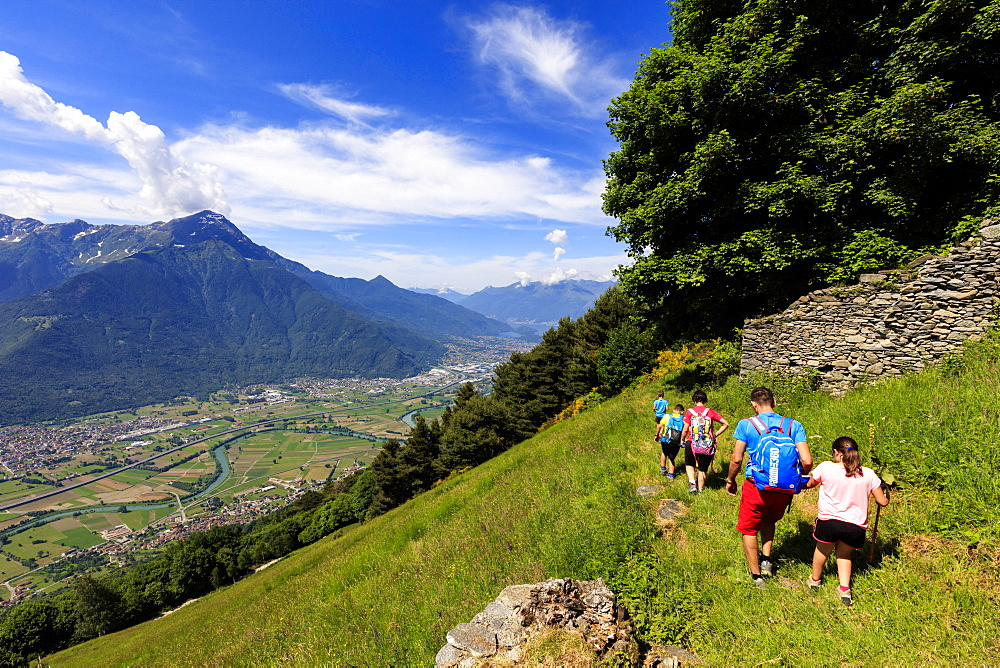 Family with children walk on footpath to Alpe Bassetta, Lower Valtellina, Sondrio province, Lombardy, Italy, Europe