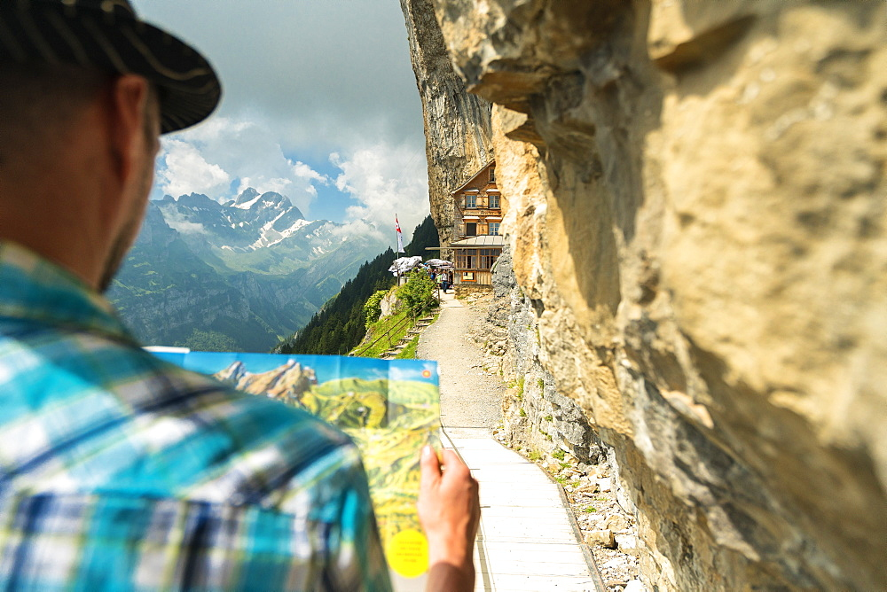 Man looks at map of hiking trails, Aescher-Wildkirchli Gasthaus, Ebenalp, Appenzell Innerrhoden, Switzerland, Europe