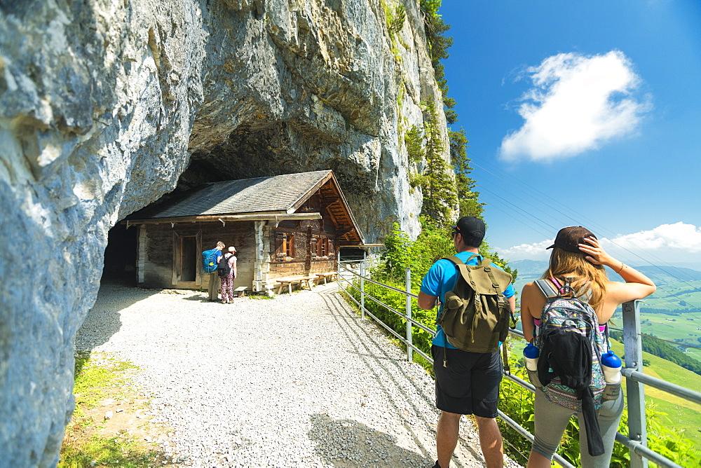 Hikers on walkway to the ancient caves, Wildkirchli, Ebenalp, Appenzell Innerrhoden, Switzerland, Europe