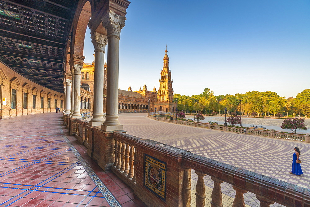 Sunrise on the old tower seen from colonnade of the semi-circular portico, Plaza de Espana, Seville, Andalusia, Spain, Europe