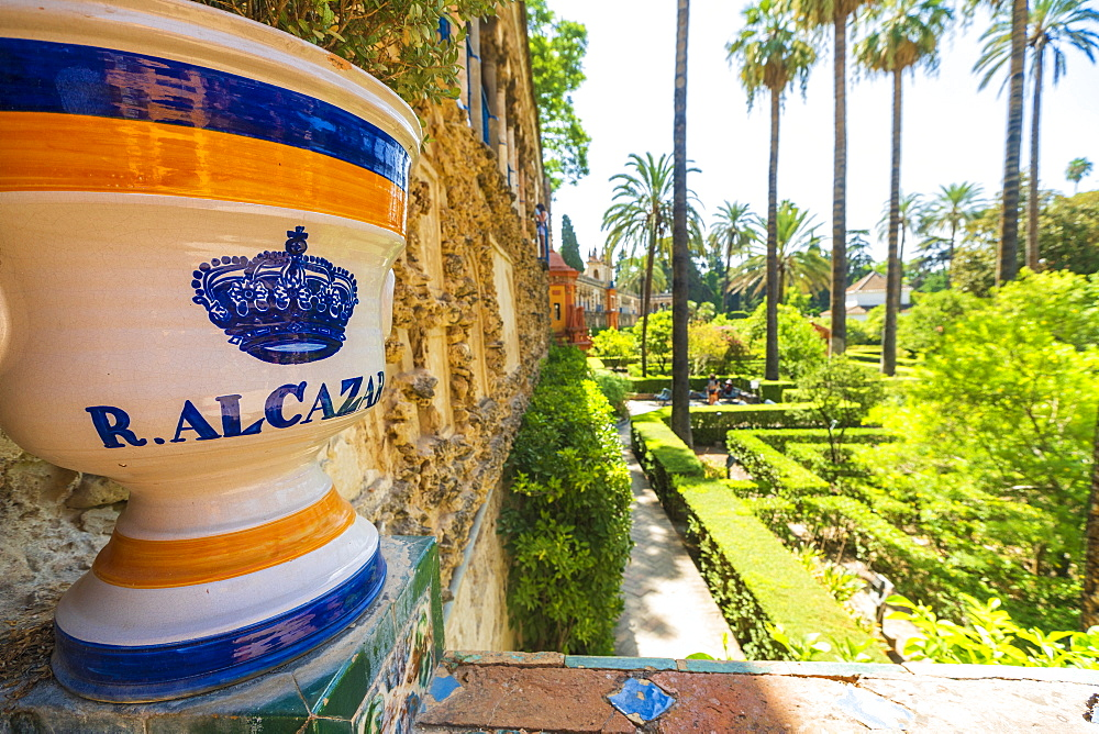 Decorated ceramic pot with royal symbol of crown on balustrade facing the lush gardens, Real Alcazar, Seville, Andalusia, Spain - 1179-3618