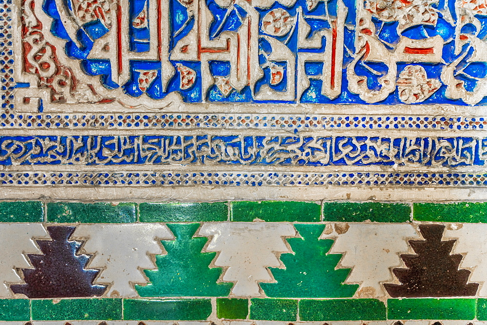 Close-up of arabic wall carving and colorful tiles with islamic inscriptions, Real Alcazar, UNESCO World Heritage Site, Seville, Andalusia, Spain, Europe