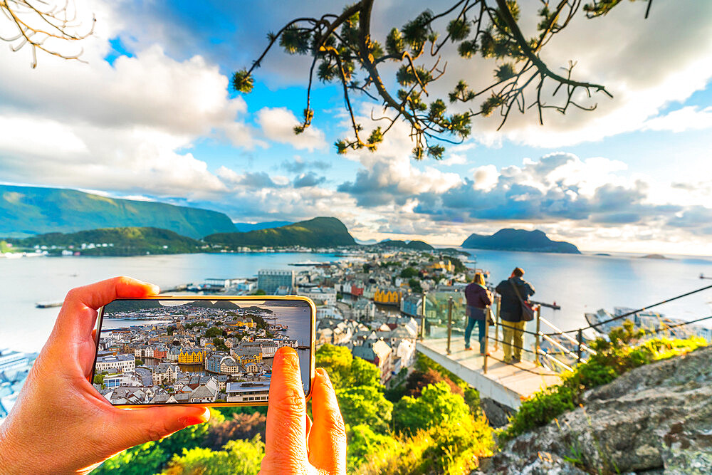 Hands holding smartphone photographing Alesund from Byrampen viewpoint, More og Romsdal county, Norway