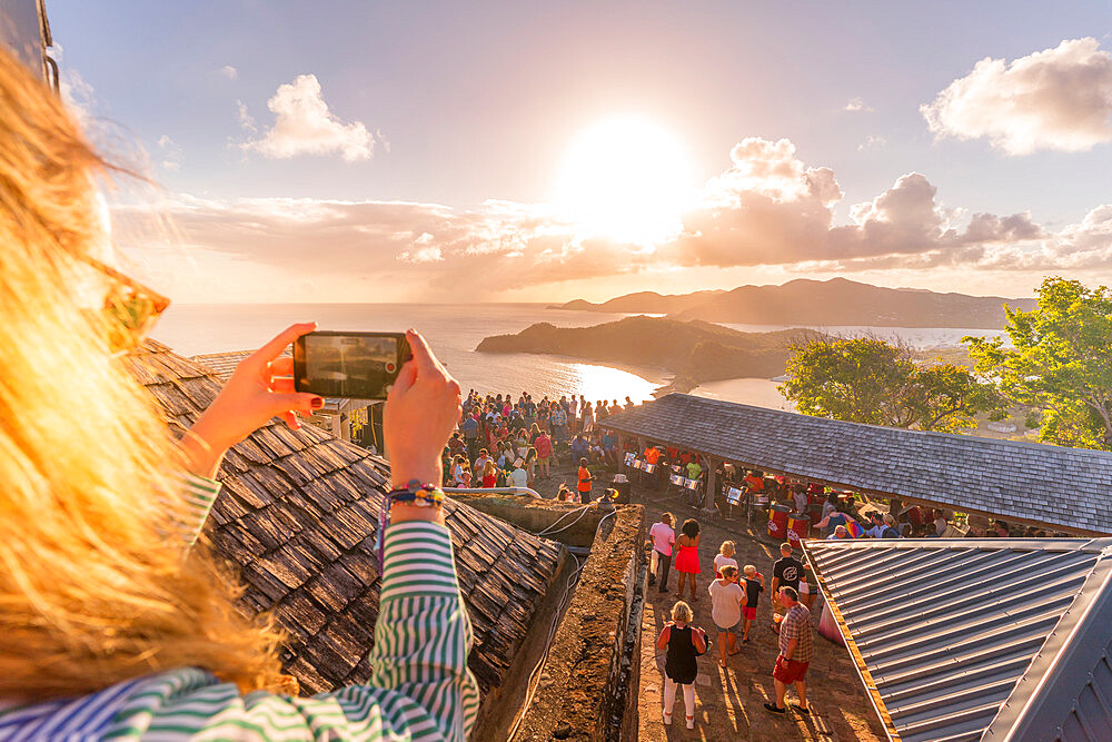 Woman takes pictures with smartphone during sunset party, Shirley Heights, Antigua, Antigua and Barbuda, Caribbean, West Indies