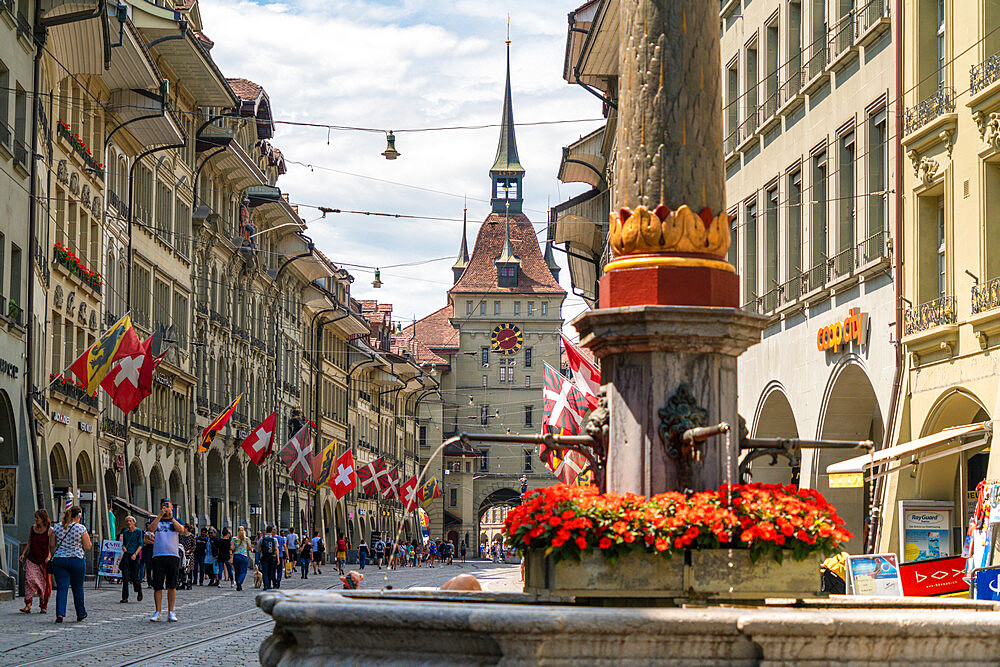 Tourists along Marktgasse, shopping street in the Old Town (Altstadt) with Kafigturm tower in background, Bern, Switzerland