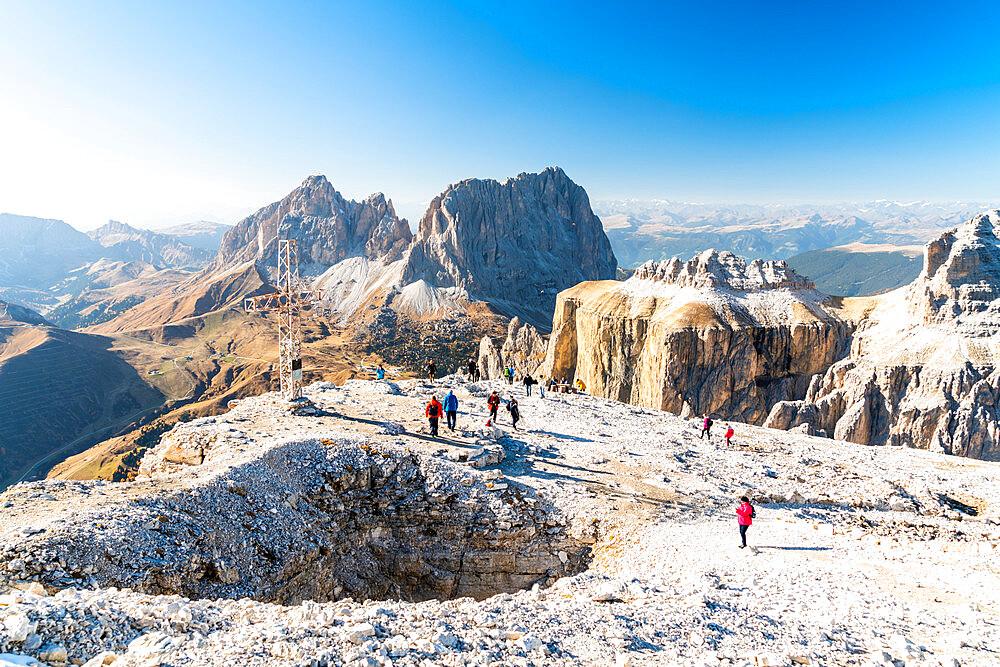 Hikers admiring Sella Pass, Sassolungo and Sassopiatto from top of Sass Pordoi, Dolomites, Trentino, Italy