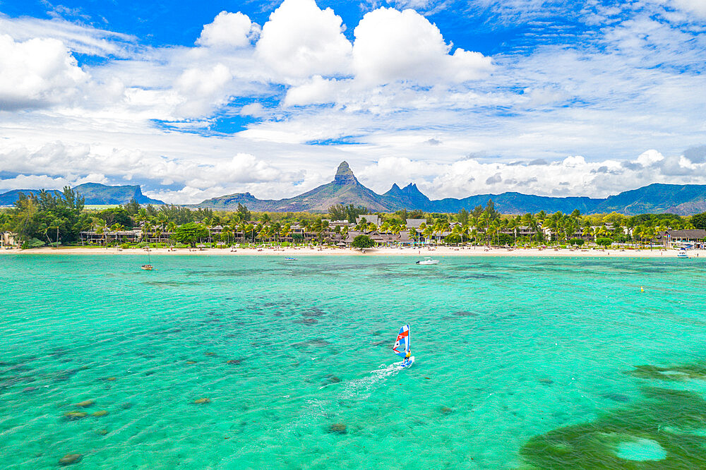 Windsurf in the lagoon facing Flic en Flac beach and Piton de la Petite Riviere Noire mount, Black River, Mauritius (drone)
