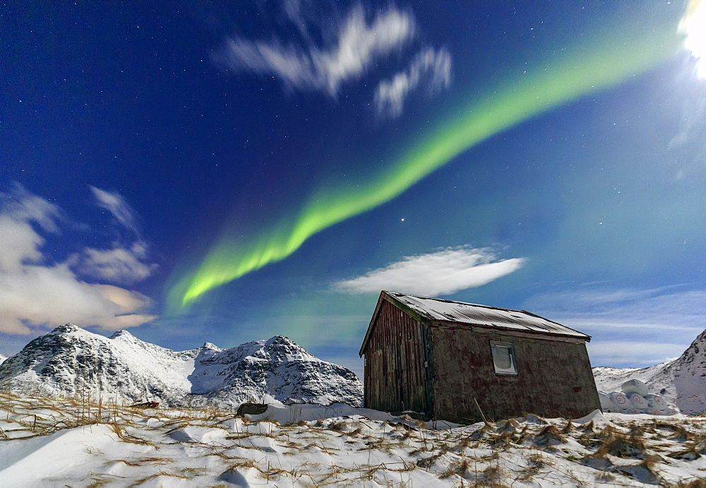Northern Lights (aurora borealis) over a small wooden house. Flakstad, Lofoten Islands, Arctic, Norway, Scandinavia, Europe