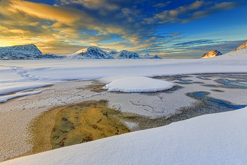 The golden sunrise reflected in a pool of the clear sea where the snow has melted, Haukland, Lofoten Islands, Arctic, Norway, Scandinavia, Europe - 1179-454