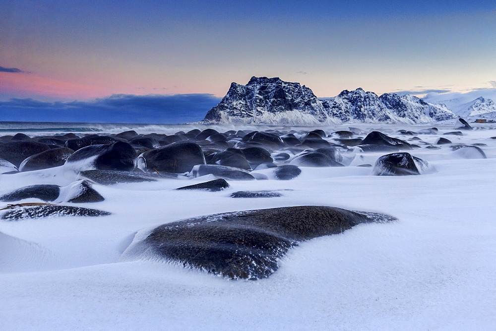 The cold wind that blows constantly shapes the snow on the rocks around Uttakleiv at dawn, Lofoten Islands, Arctic, Norway, Scandinavia, Europe
