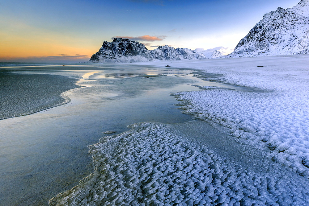 Dawn illuminates the beach covered with frozen snow in the cold sea of Uttakleiv, Lofoten Islands, Arctic, Norway, Scandinavia, Europe