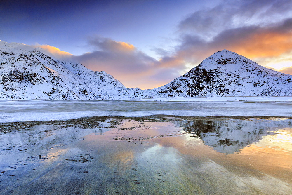 Sunrise on Uttakleiv beach surrounded by snow covered mountains reflected in the cold sea, Lofoten Islands, Arctic, Norway, Scandinavia, Europe