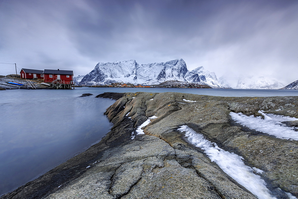 Typical landscape of Hamnoy with red houses of fishermen and the snowy mountains, Lofoten Islands, Northern Norway, Scandinavia, Arctic, Europe