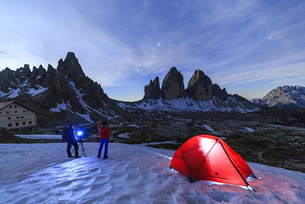 Hikers admire the Three Peaks of Lavaredo before spending the night in the tent, Sesto, Dolomites, Trentino-Alto Adige, Italy, Europe