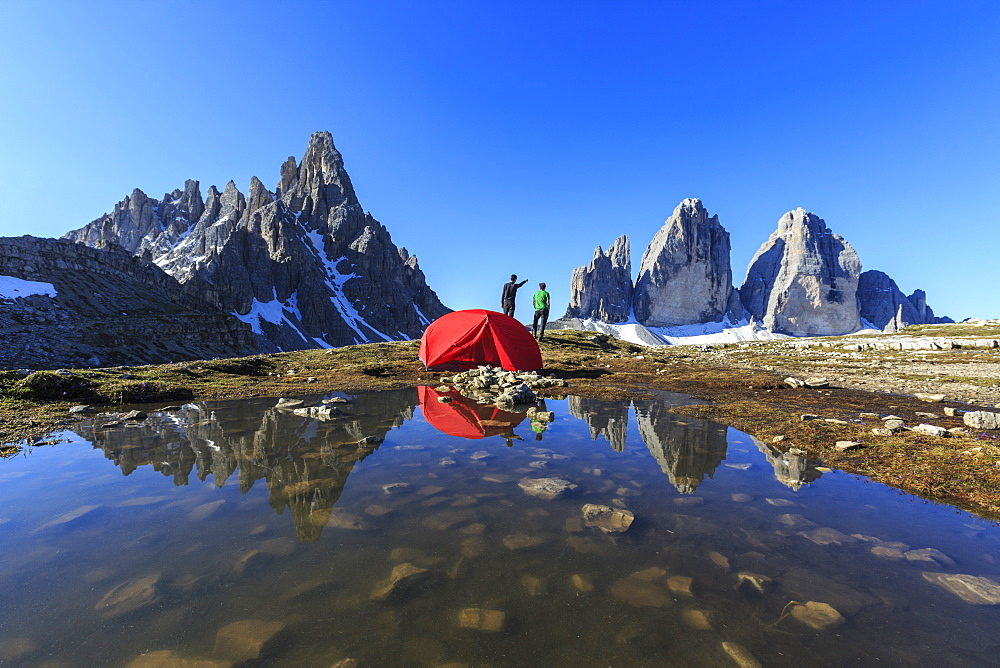 Hikers camped for the night admire the Three Peaks of Lavaredo on awakening, Sesto, Dolomites, Trentino-Alto Adige, Italy, Europe