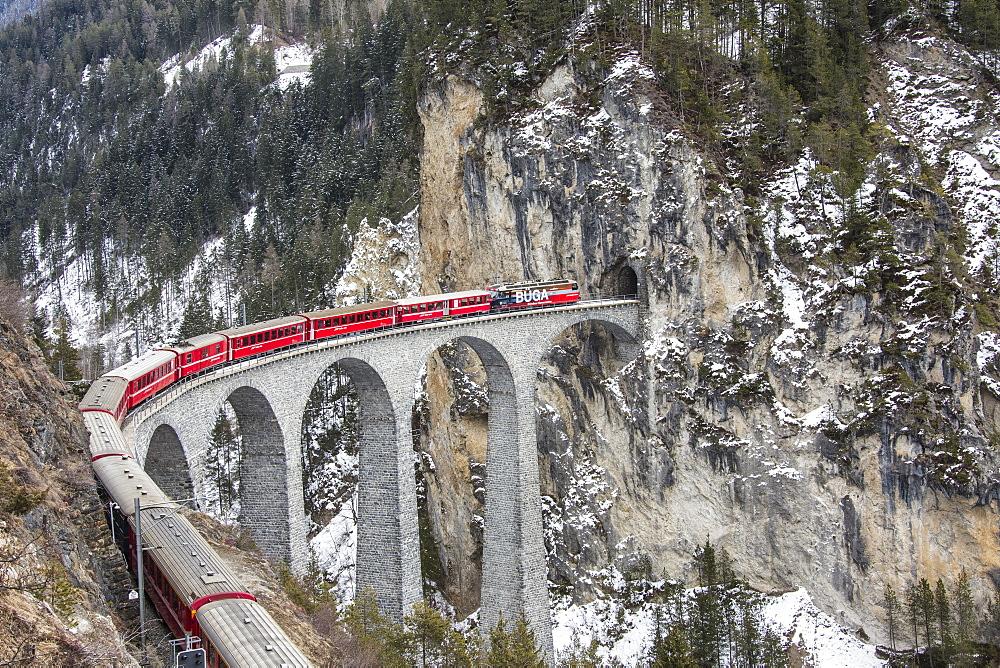Bernina Express passes over Landwasser Viaduct, UNESCO World Heritage Site, and snowy woods, Filisur, Canton of Grisons (Graubunden), Switzerland, Europe