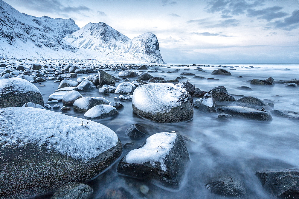 Rocks in the cold sea and snow capped mountains under the blue light of dusk, Unstad, Lofoten Islands, Arctic, Northern Norway, Scandinavia, Europe