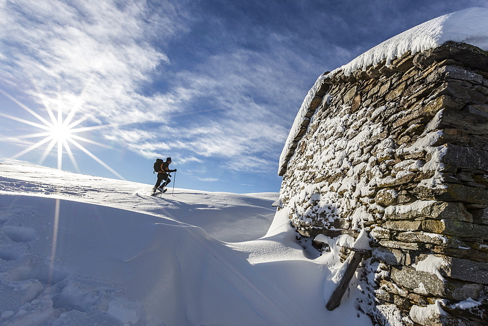 Snowshoe hiker walking near snow covered hut, Motta di Olano, Gerola Valley, Valtellina, Orobie Alps, Lombardy, Italy, Europe