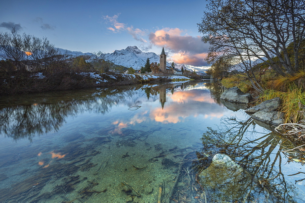 Dawn illuminates the snowy peaks and the bell tower reflected in Lake Sils, Engadine, Canton of Graubunden, Switzerland, Europe