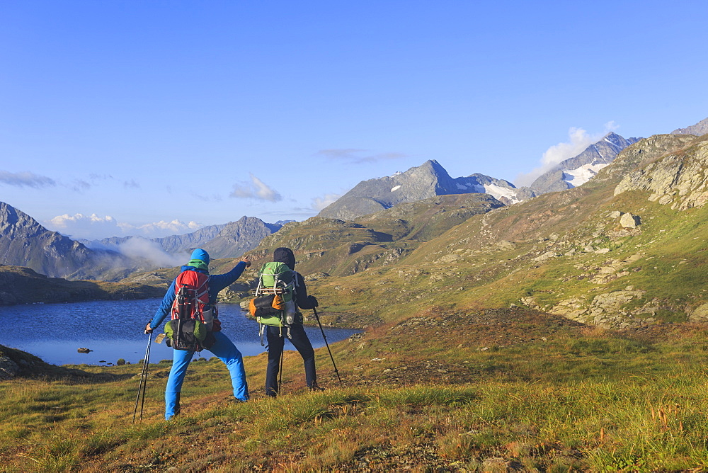 Hikers admire the peaks and the blue alpine lake, Minor Valley, High Valtellina, Livigno, Lombardy, Italy, Europe