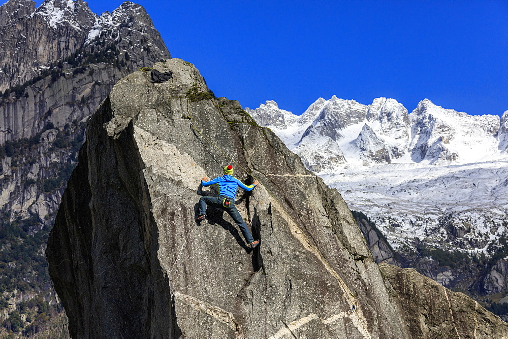 Climber on steep rock face, in the background blue sky and snowy peaks of the Alps, Masino Valley, Valtellina, Lombardy, Italy, Europe