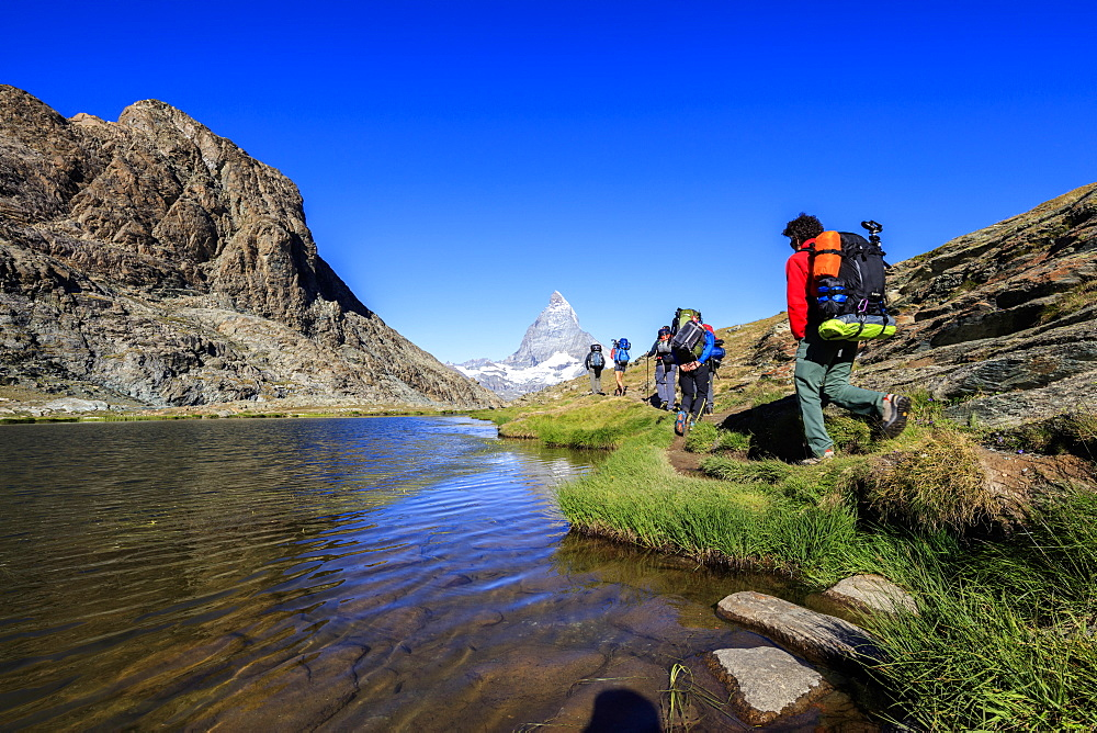 Hikers proceed on the shore of Lake Riffelsee with the Matterhorn in the background, Zermatt, Canton of Valais, Switzerland, Europe