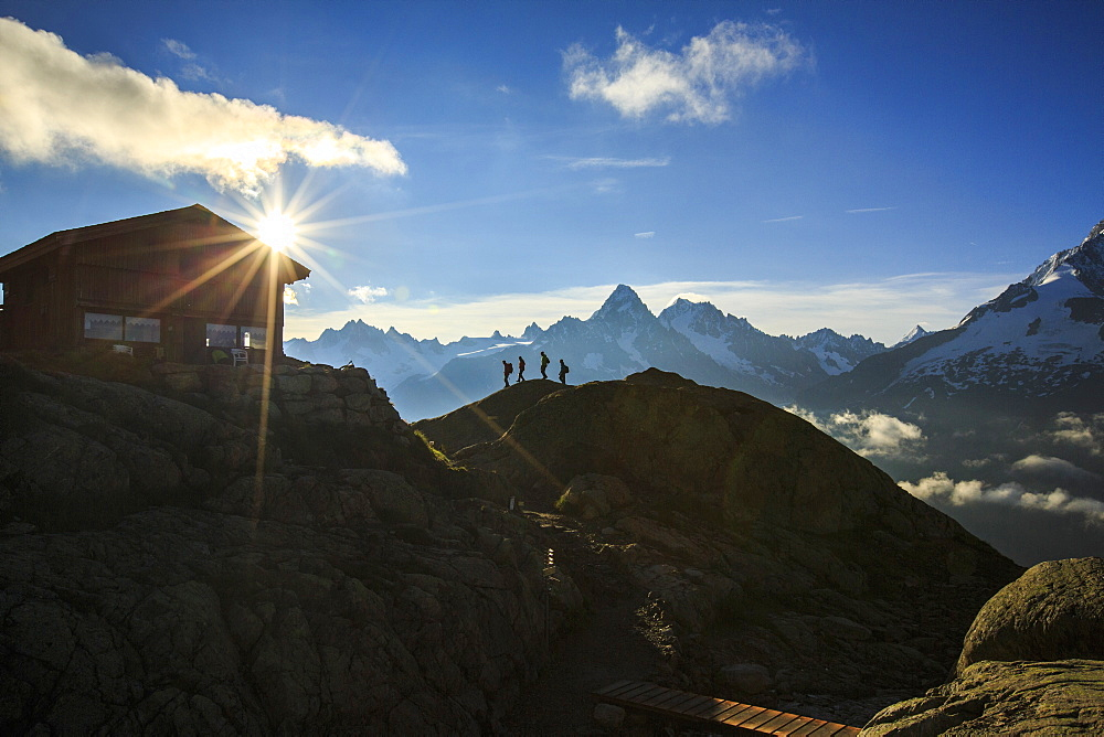 Hikers proceed towards Refuge of Lac de Cheserys with the sun just risen, Chamonix, Haute Savoie, French Alps, France, Europe