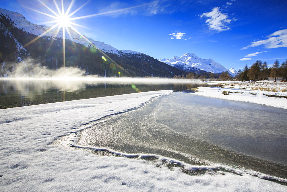 Rays of winter sun illuminate Lake Silvaplana still partially frozen, Maloja, Engadine, Graubunden Canton, Switzerland, Europe