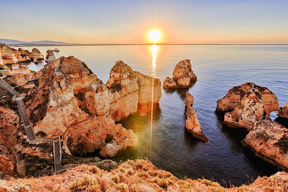 Golden sunrise on the red cliffs of Ponta Da Piedade, Lagos, Algarve, Portugal, Europe