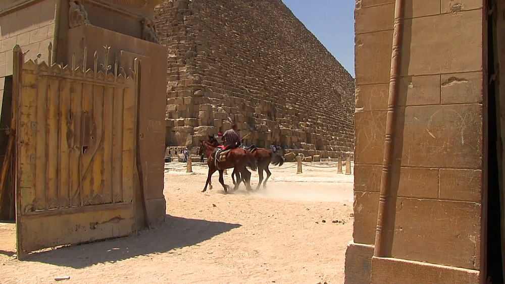 The Pyramid of Khufu tilt down to horses galloping past an ancient gate, Egypt, South Africa - 1182-109