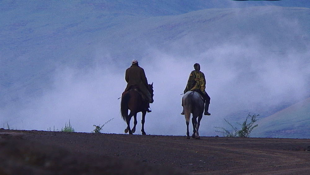 Two Basotho, sotho men riding horses in the early morning mist in Lesotho mountains, Africa